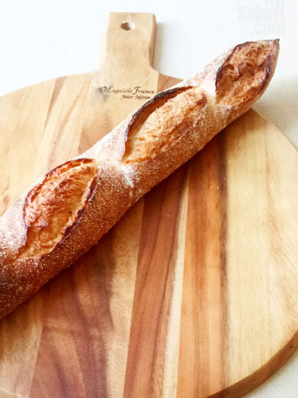An artisan sourdough baguette on a wooden serving platter