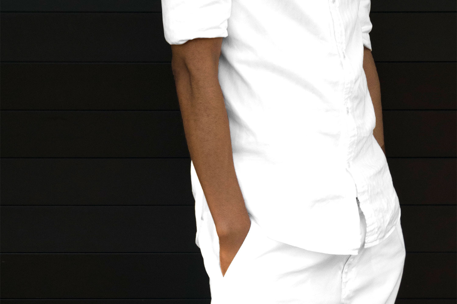 KG wears casually styled classic whites in front of a black door